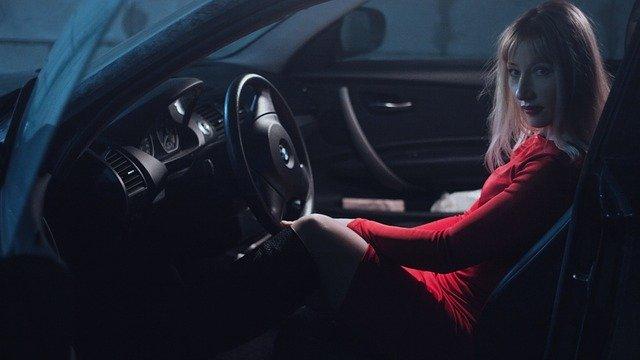 dívka v autě v červených šatech